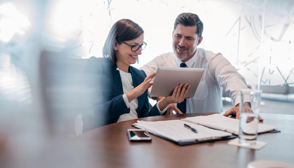 confident business people using tablet at table