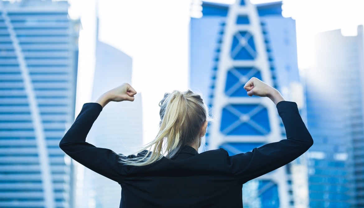 energetic female business leader flexes in front of cityscape