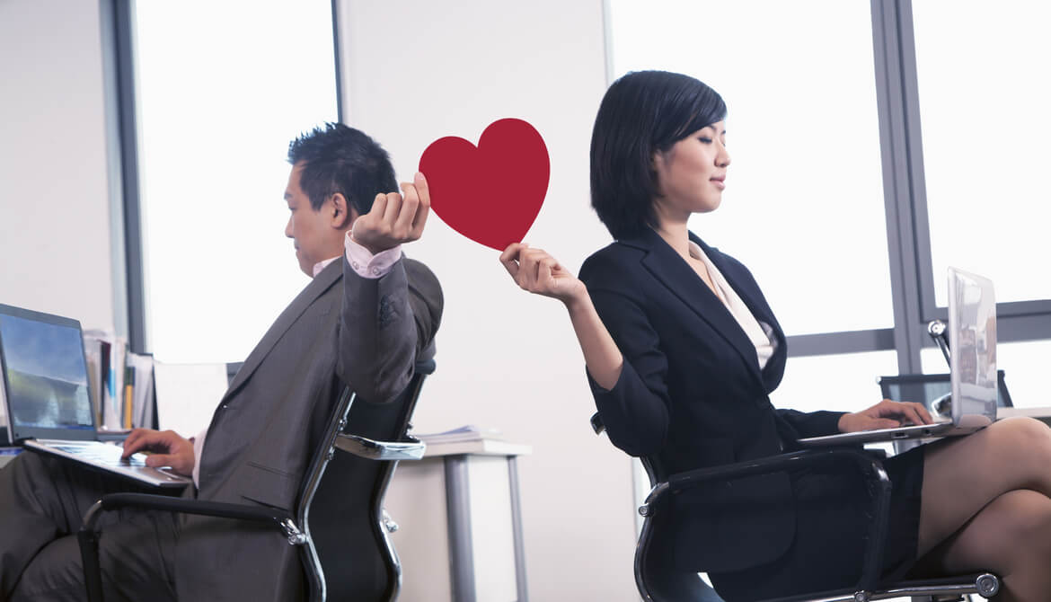 executives passing a red paper heart between their workspaces