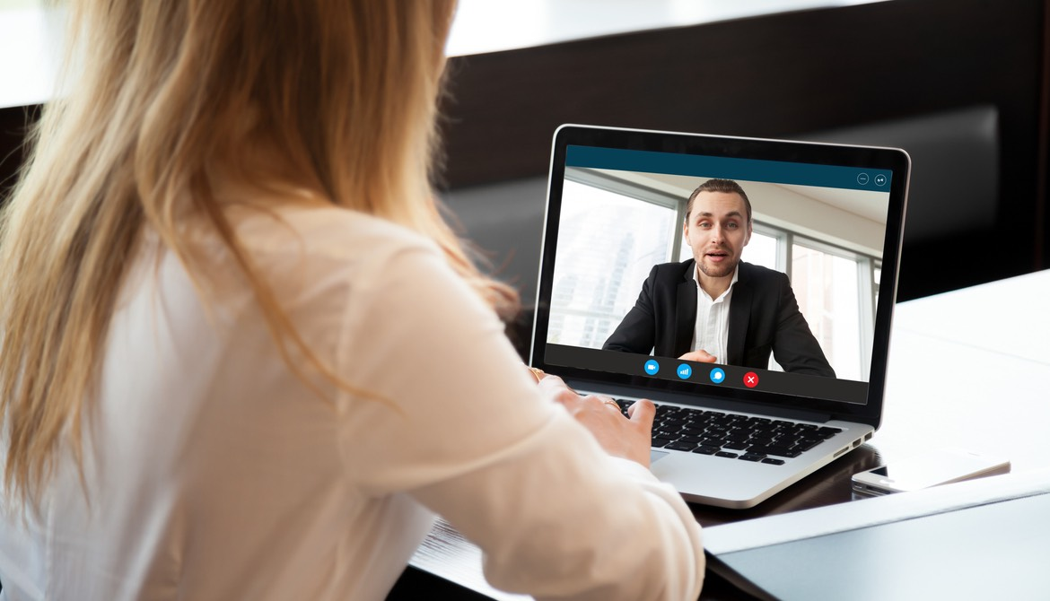 Woman using laptop to teleconference with a male executive