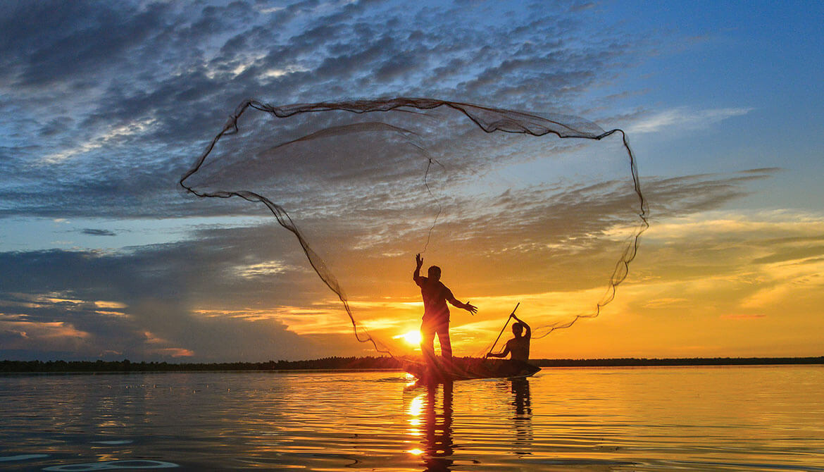 two fishermen in rowboat casting a wide net into water