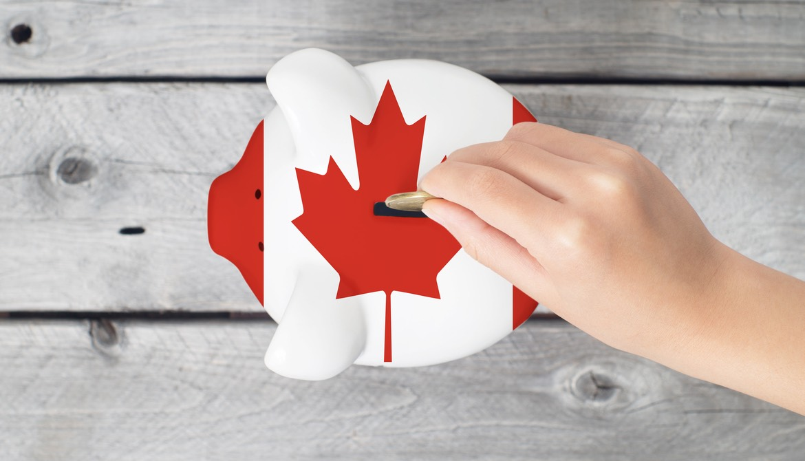 hand dropping coin into piggy bank painted to look like Canadian flag