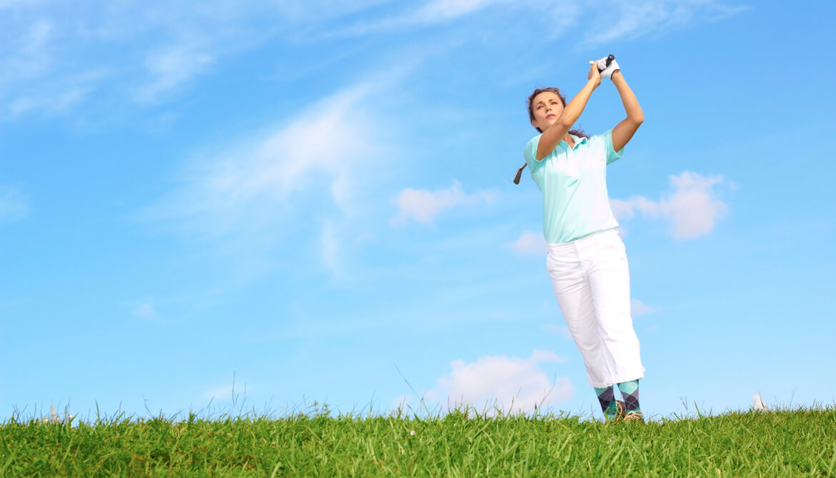 female golfer following through swing in the rough in front of blue sky