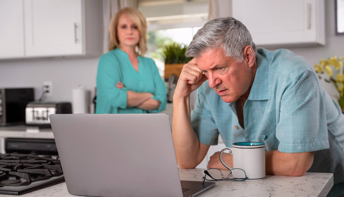 senior couple kitchen laptop financial concerns