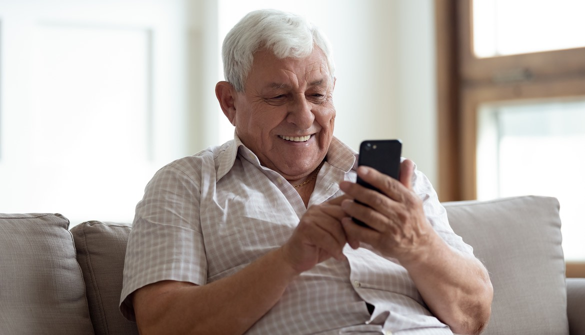 older man using smartphone on couch