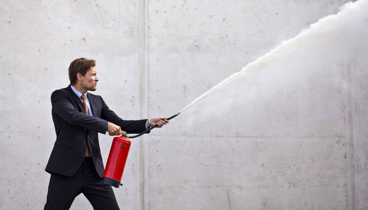 executive using fire extinguisher