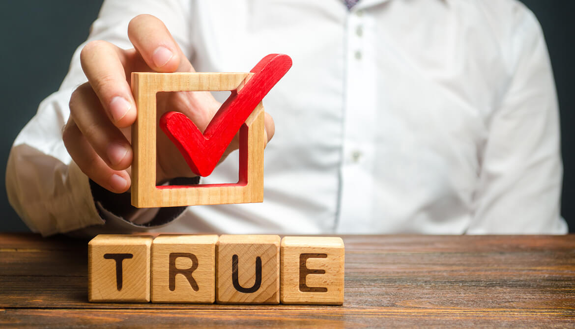 man holds red check mark over the word true