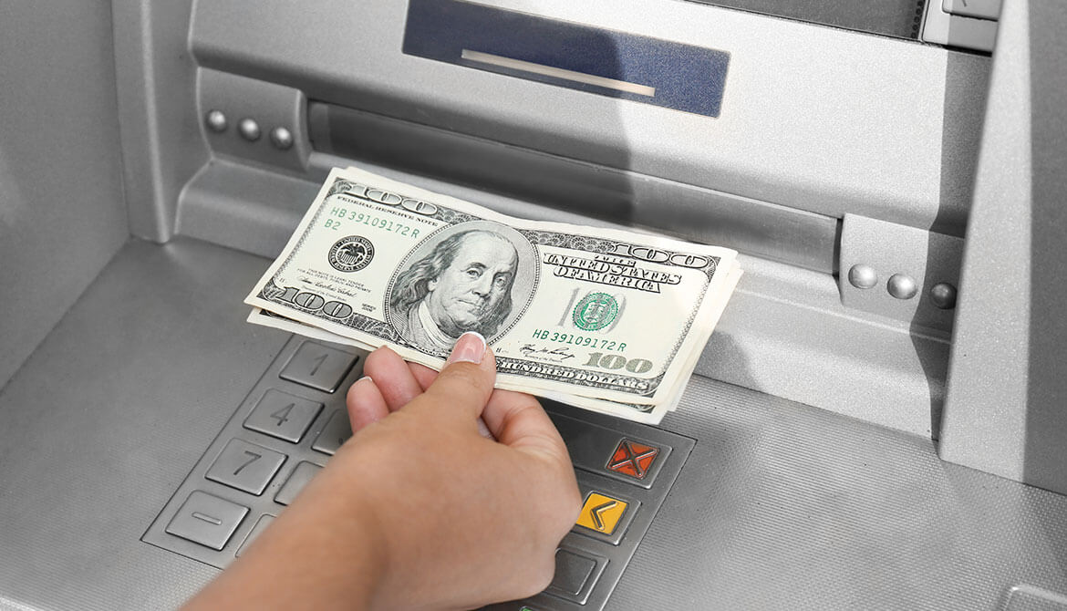 hand withdrawing $100 bills from ATM