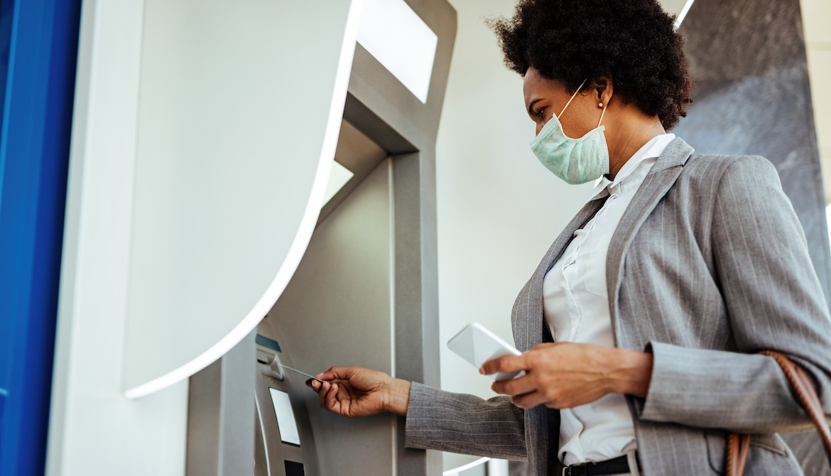 masked woman using atm during pandemic
