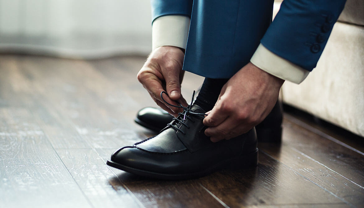 businessman in blue suit bending down to tie laces of black dress shoe
