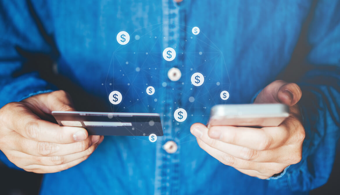 man using smartphone with credit card and dollar signs