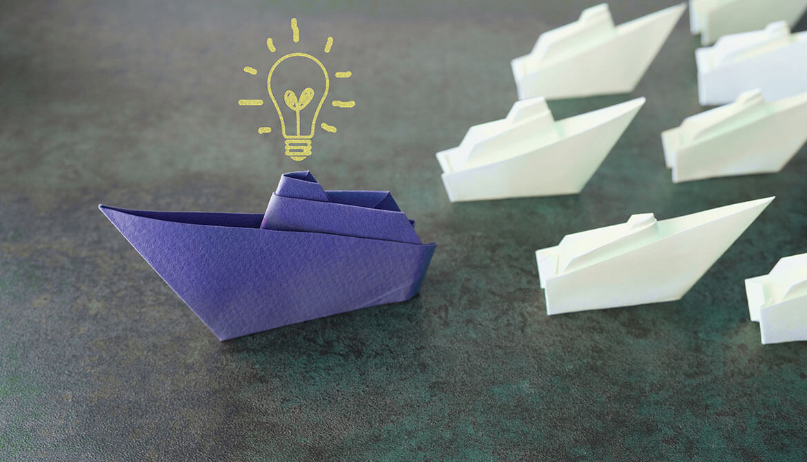 white paper boats going in different direction than bigger blue paper boat with drawing of light bulb above it