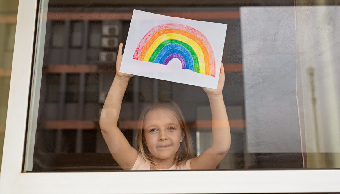 child in window holding up colored drawing of rainbow of hope