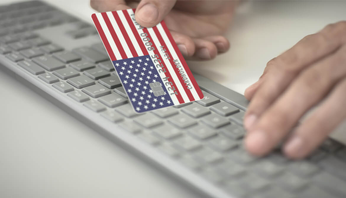 man making online payment using credit card with U.S. flag keyboard