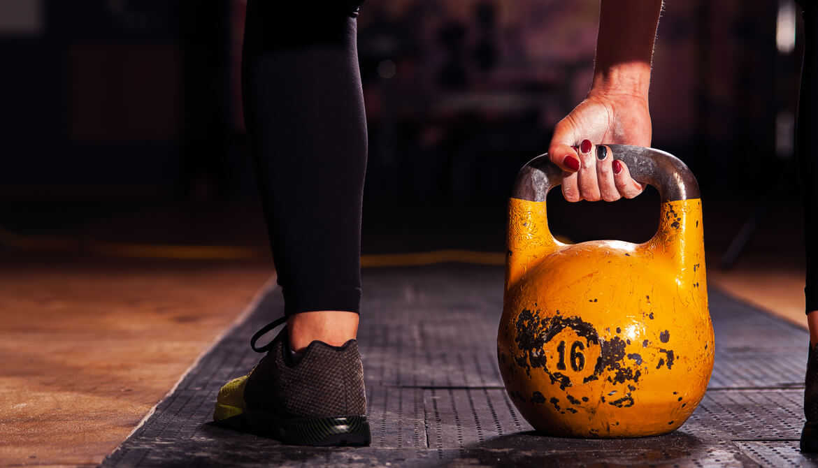 athlete exercising with a yellow kettlebell