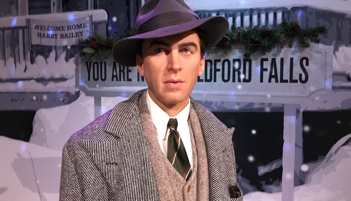 Jimmy Stewart figure in front of Bedford Falls sign from It's a Wonderful Life