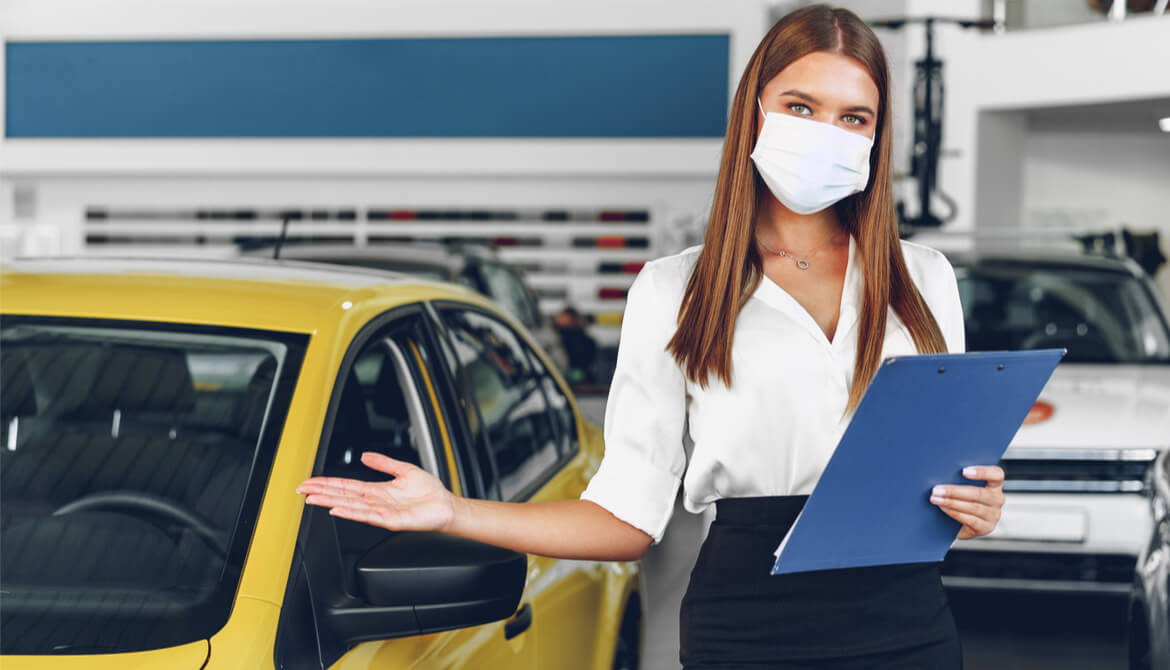 female car salesperson holding arm out by car