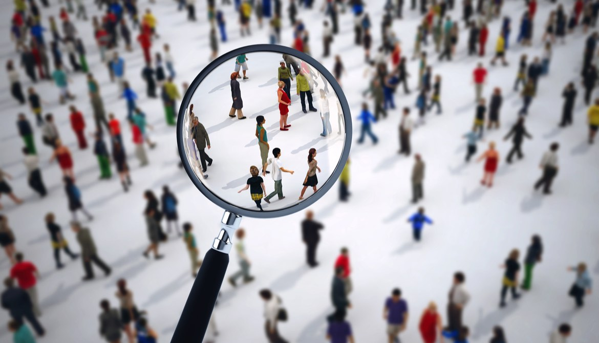 searching crowd of diverse people with magnifying glass for job candidate