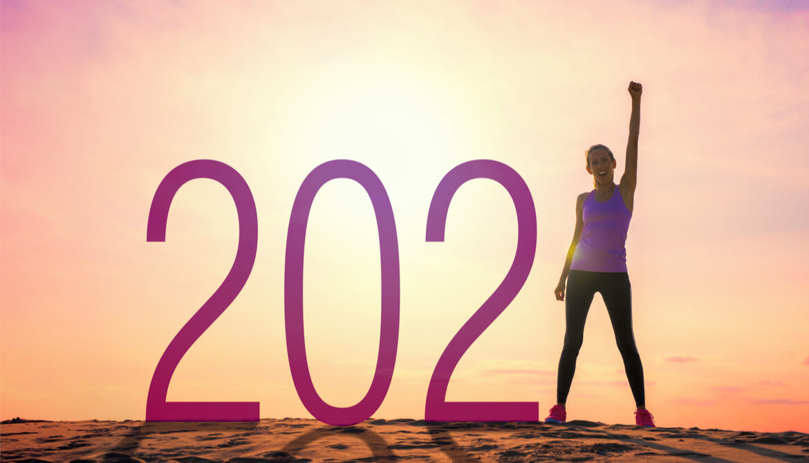 woman with arm up and fist next to a 2021 sign in the sun