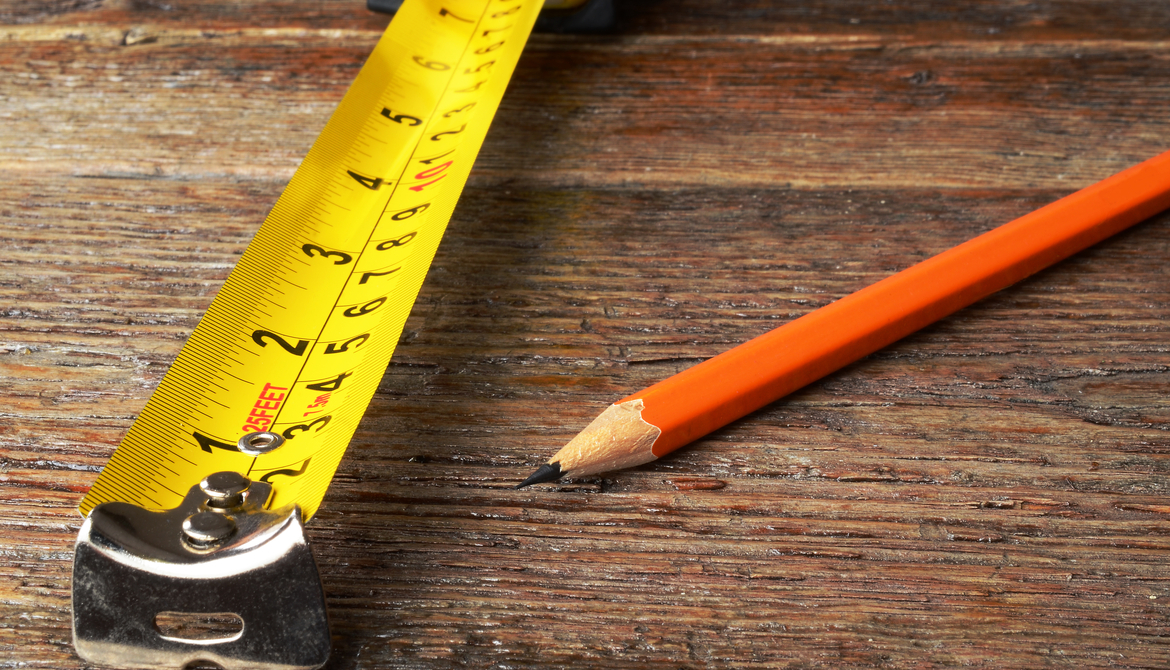 yellow tape measure and orange wooden pencil