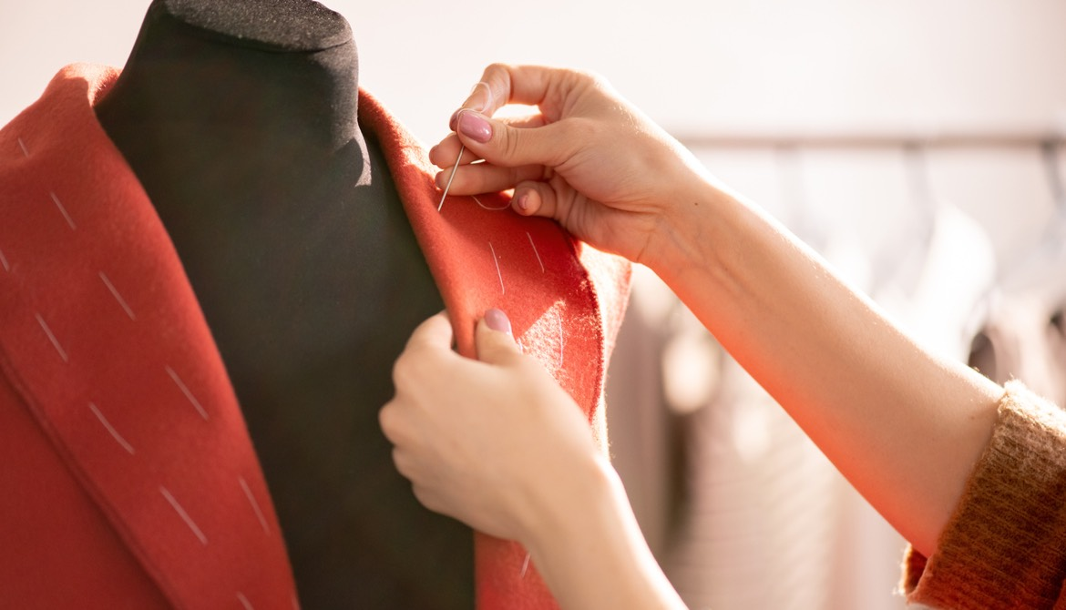 seamstress working on a coat on a mannequin