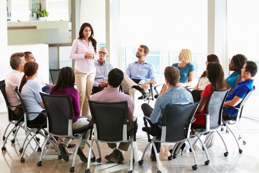 woman standing and speaking confidently in a meeting