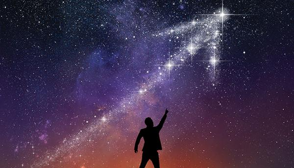 silhouette of a person pointing up at a galaxy in the shape of an upward arrow in the night sky