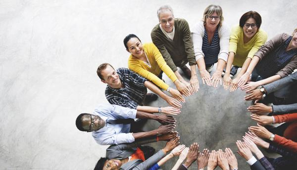 diverse group of happy people putting their hands into the center to form a circle