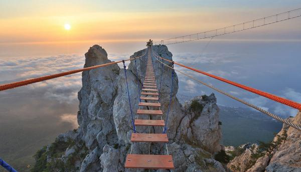 Precarious rope bridge leading to a mountain peak