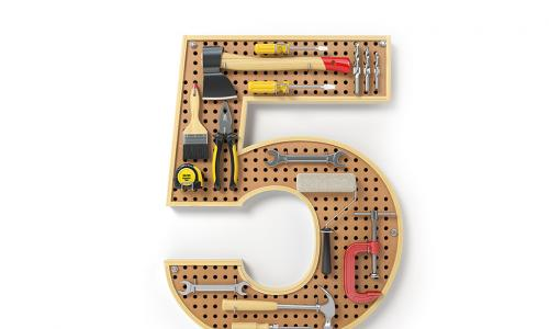 A pegboard in the shape of a number 5 with tools on it