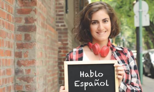 Young woman holding a chalk slate that reads Hablo Espanol