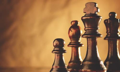 set of polished brown wooden chess pieces on a matching board