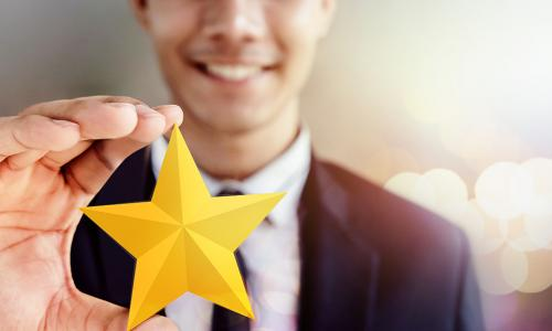 Happy Businessman in black suit Smiling and Showing a Golden Star in Hand