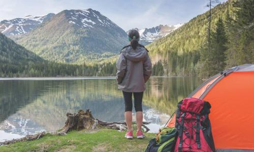 Woman at campsite looks over a lake to a distant mountain peak