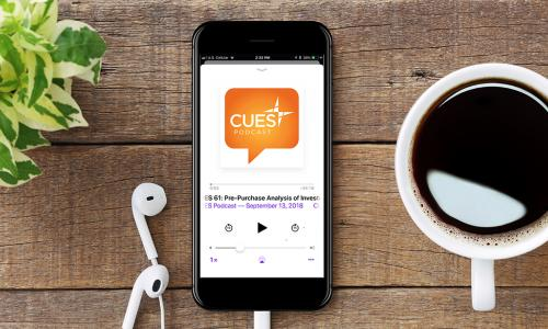 CUES Podcast on a mobile phone next to a cup of coffee