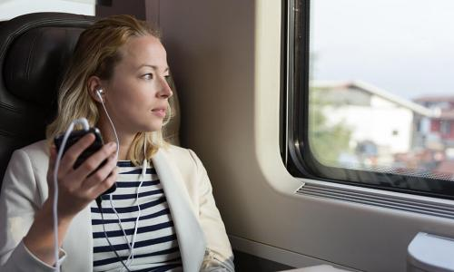 Woman on train listening to CUES podcasts