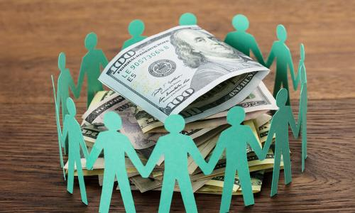 green paper dolls in a circle around cash