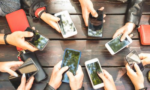 group of millennials' arms with phones around table