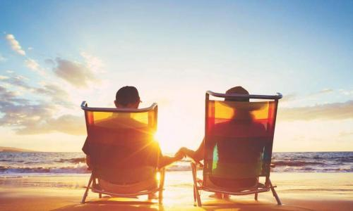 Retired couple sitting on chairs at the beach at sunset