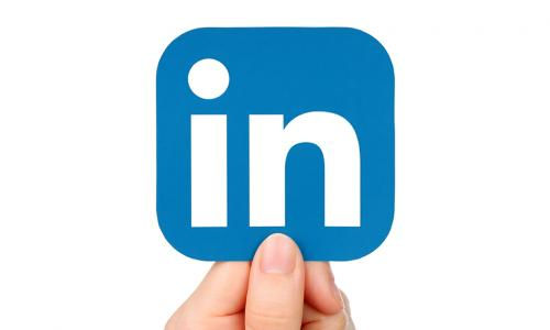 Hand holding up a blue LinkedIn icon