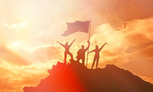 Group of people raising a flag at the top of a mountain symbolizing high performance and success