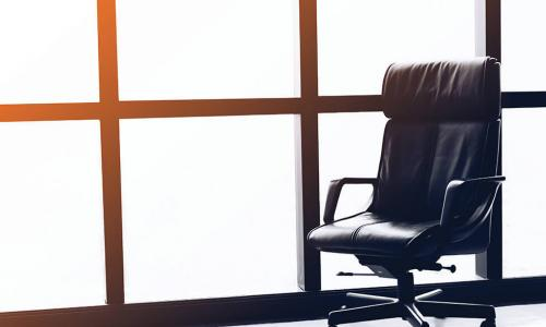 Empty executive chair in front of office window