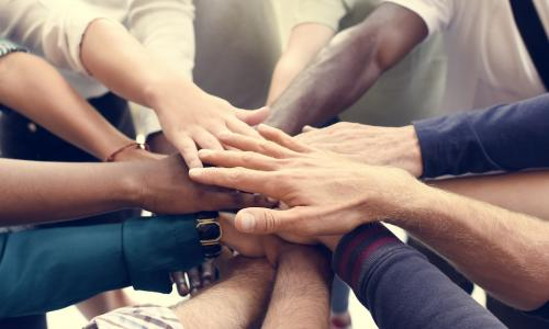 hands together in a circle as for teamwork and diversity