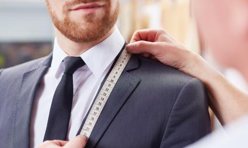 executive getting custom-fitted for a suit