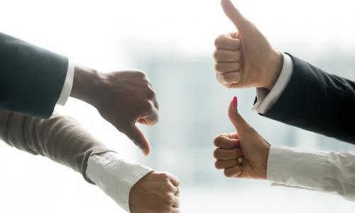 Hands of diverse business people showing two thumbs up and two thumbs down, suggesting equal opposing forces