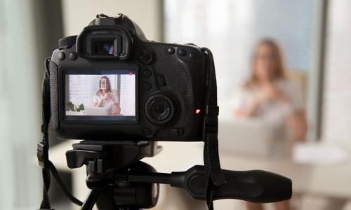 Camera on a tripod recording a video of a businesswoman