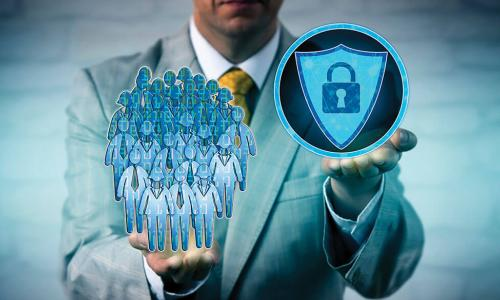 businessman holding a padlock and shield icon representing cybersecurity in one hand and an illustrated group of employees in the other