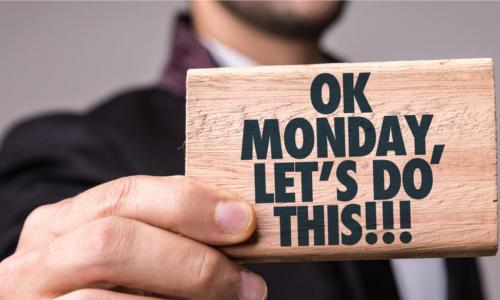 man holds sign that says Ok Monday Lets Do This