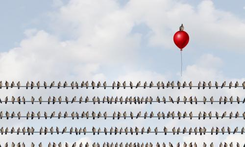 birds on a wire with one rising above the crowd on a red balloon
