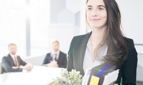 smiling young businesswoman holding box of personal belongings leaving office after quitting job